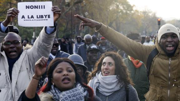 "A man holds a placard reading ""No to slavery in Libya"" during a march against ""slavery in Libya"" on November 18, 2017 in Paris."