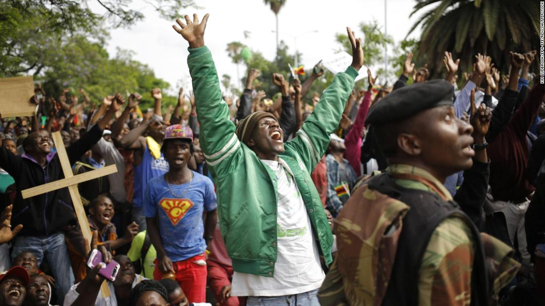 People in Harare react as they see a military helicopter fly overhead during protests against Mugabe on November 18.