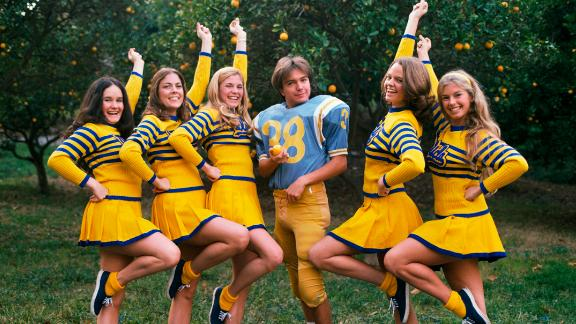 Ever the ladies' man, Cassidy poses in a UCLA football uniform flanked by five cheerleaders.