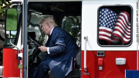 "President Donald Trump examines a fire truck from Wisconsin-based manufacturer Pierce on the South Lawn during a ""Made in America"" product showcase event at the White House in Washington, DC, on July 17, 2017.  / AFP PHOTO / Olivier Douliery        (Photo credit should read OLIVIER DOULIERY/AFP/Getty Images)"