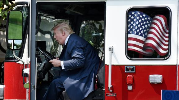 President Trump plays in a fire truck as the media looks on. Critics say Americans have lowered their presidential standards since Trump took office.