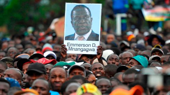 People hold a portrait of Zimbabwe