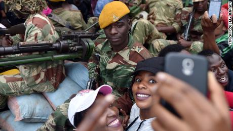 A Zimbabwean Defence Force soldier poses for selfie-pictures with two women as they take part in a march in the streets of Harare, on November 18, 2017 to demand to the 93 year-old Zimbabwe's president to step down.