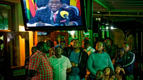 """At a bar in Harare, people watch Mugabe give a televised address to the nation on Sunday, November 19. Mugabe ended <a href=""""http://www.cnn.com/2017/11/19/africa/zimbabwe-mugabe-party-meeting/index.html"""" target=""""_blank"""">the address</a> without giving his resignation."""