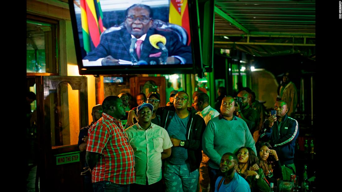 "At a bar in Harare, people watch Mugabe give a televised address to the nation on Sunday, November 19. Mugabe ended <a href=""http://www.cnn.com/2017/11/19/africa/zimbabwe-mugabe-party-meeting/index.html"" target=""_blank"">the address</a> without giving his resignation."