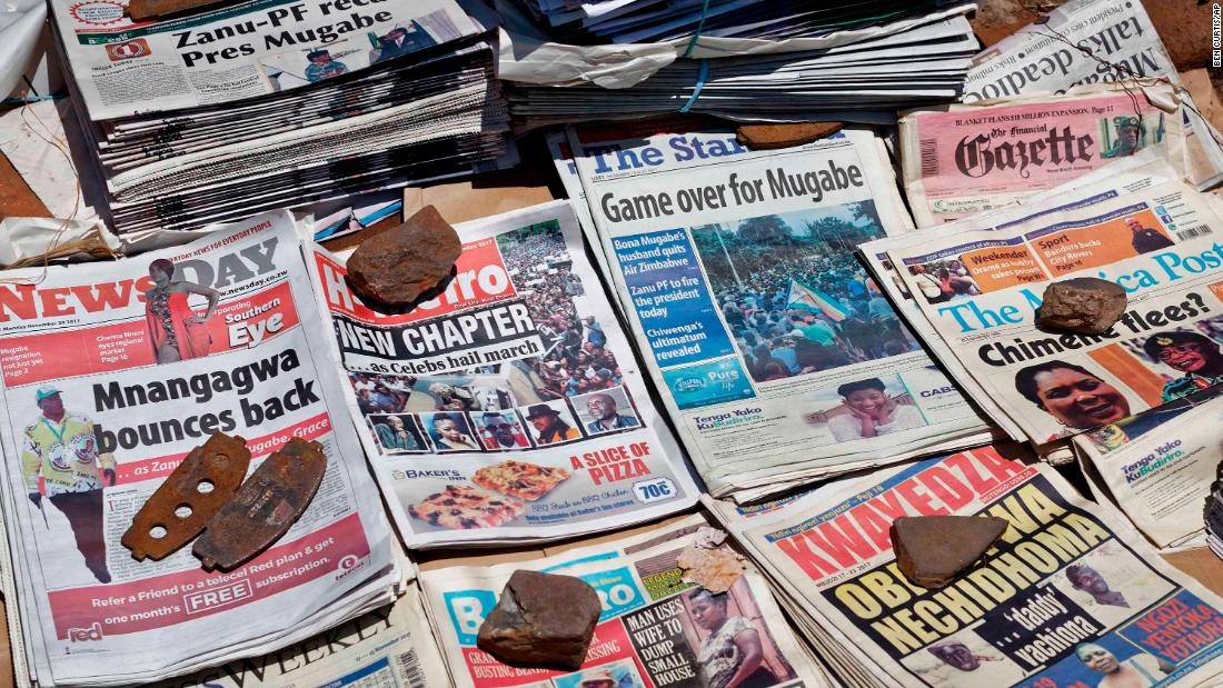 Newspapers are held in place with rocks at a newsstand in Harare on November 20.