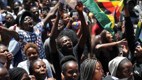 A man holding a flag of Zimbabwe takes part in a demonstration of University of Zimbabwe's students, on November 20, 2017 in Harare, to demand the withdrawal of Grace Mugabe's doctorate and refused to sit their exams as pressure builds on Zimbabwe's President Robert Mugabe to resign.