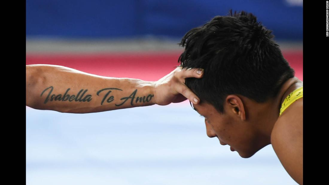 "Peruvian wrestler Sixto Auccapina, right, is held at arm's length by Colombia's Hernan Guzman during the Bolivarian Games on Tuesday, November 14. Guzman's tattoo reads ""Isabella Te Amo"" (""I love you Isabella"")."