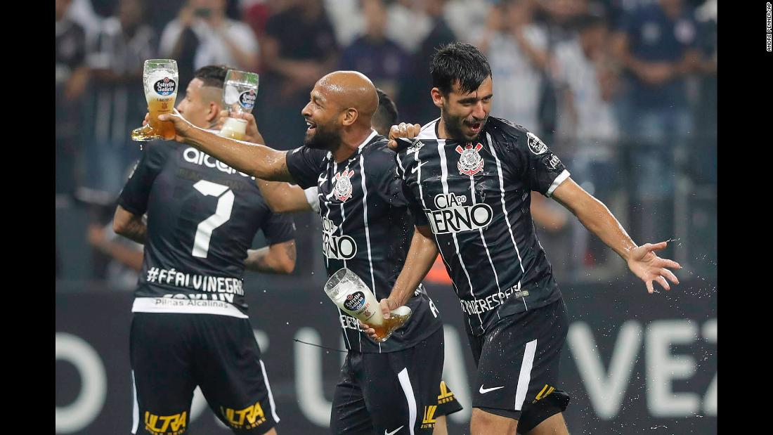 Soccer players from the Brazilian club Corinthians carry drinks as they celebrate clinching the league title in Sao Paulo, Brazil, on Wednesday, November 15.