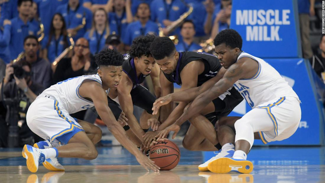 Players from UCLA and Central Arkansas battle for a loose ball during a college basketball game in Los Angeles on Wednesday, November 15.