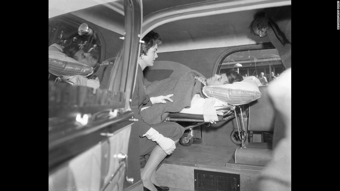 Accompanied by his wife, Jackie, Kennedy leaves the hospital to be with family for the holidays two months after the 1954 spinal fusion surgery. It took that long to overcome the complications.