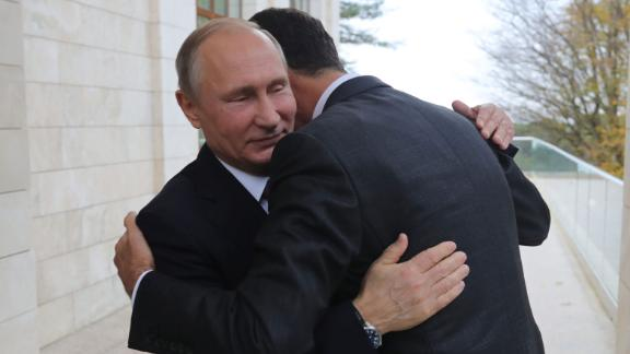 Putin (L) embraces Assad during their meeting in Sochi last month.