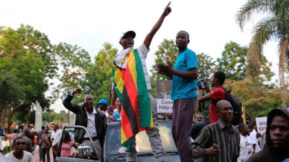 Zimbabweans raise their fists at the news of Robert Mugabe
