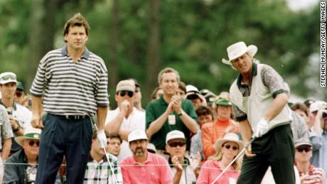 Faldo (left) watches playing partner Greg Norman tee off on the first hole during third round of play in the Masters.