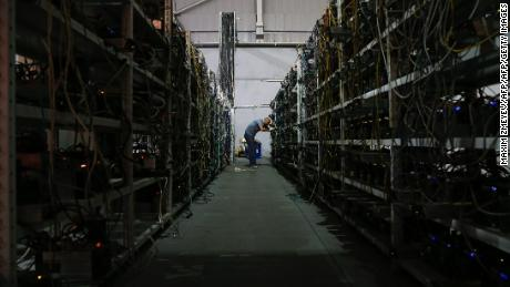 "Russia's crypto-businessman Dmitry Marinichev's virtual currencies mining farm operates in a former Soviet-era car factory warehouse in Moscow, July 26, 2017. ""The form of currency we are used to is about to disappear,"" predicts Dmitry Marinichev in the deafening hum of hundreds of computers stacked on shelves hard at work mining for crypto money. Individuals, or firms like Marinichev's, provide the computing power to run the so-called blockchain which records the world's virtual money transactions. In return for providing that service they receive virtual money, of which bitcoin is the most popular, as payment -- a process bitcoiners call ""mining"". / AFP PHOTO / MAXIM ZMEYEV / TO GO WITH AFP STORY BY Maxime POPOV        (Photo credit should read MAXIM ZMEYEV/AFP/Getty Images)"
