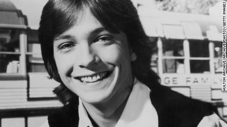 1970:  Headshot portrait of American pop musician and actor David Cassidy smiling and holding a guitar.  (Photo by Hulton Archive/Getty Images)