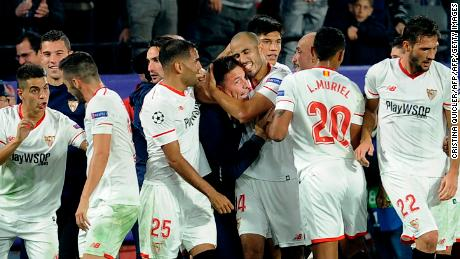 Sevilla players run to celebrate with Eduardo Berizzo following Guido Pizarro's late equalizer.