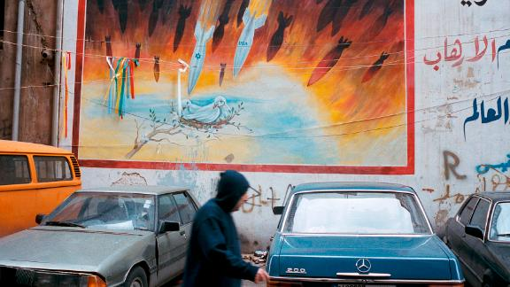A man passes a mural painted on a wall in southern Beirut in 2006.