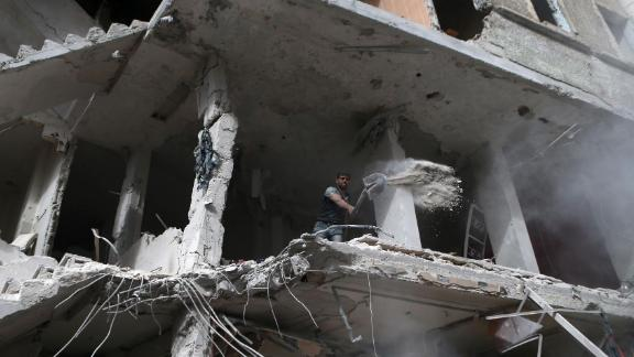 A Syrian shovels away debris from the higher floor of a building that was reportedly shelled by regime forces in rebel-held Eastern Ghouta.