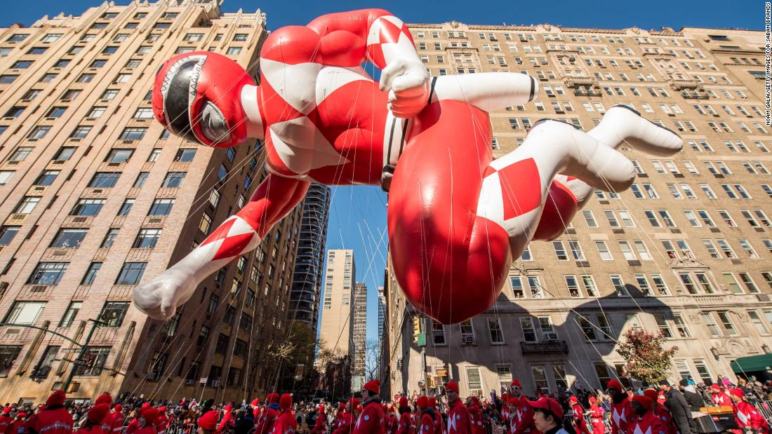 A Power Ranger balloon is held by handlers.