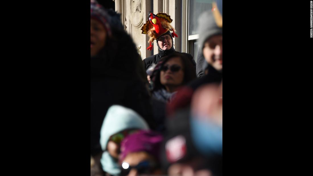 A paradegoer wears a turkey hat.