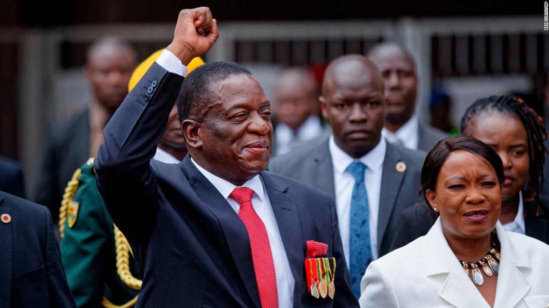 Mnangagwa greets the crowd as he arrives at the inauguration with his wife.