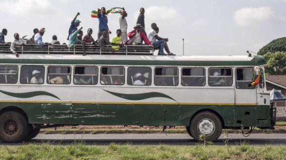 Zimbabweans make their way to the National Sports Stadium by bus.