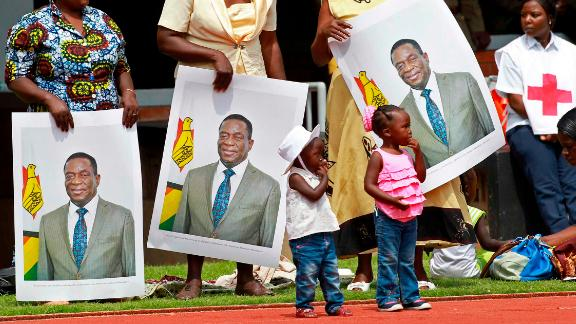 People hold portraits of Mnangagwa before the start of the inauguration.
