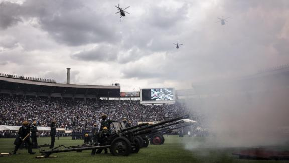 Helicopters fly over the National Sports Stadium as a battery of artillery fires salvos during the ceremony.