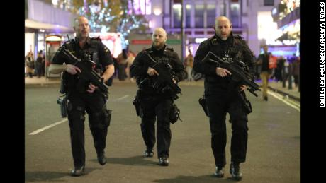 Armed police patrol near Oxford Street as they respond to an incident on Friday in London.