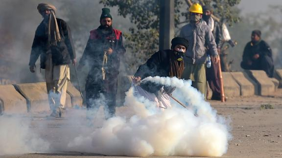 A Pakistani protester of the Tehreek-i-Labaik Yah Rasool Allah Pakistan (TLYRAP) religious group throws a tear gas shell back towards police during a clash in Islamabad on November 25, 2017.