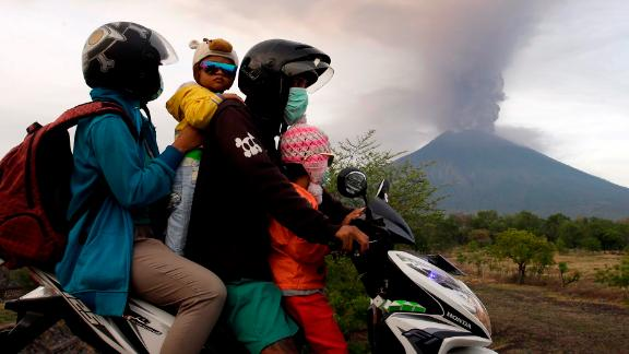 A family on a motorcycle passes by the Mount Agung volcano erupting in the background.