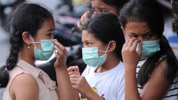 Young people put on masks due to ash in the air.
