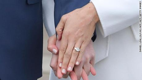 Britain's Prince Harry stands with his fiancée Meghan Markle as she shows off her engagement ring .
