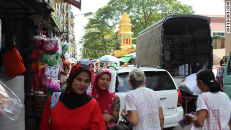 Two women wearing veils walk along a street in central Yangon with a Hindu temple in the background on September 21, 2017.