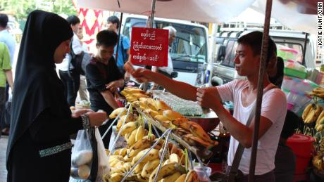 A woman wearing a veil buys bananas in central Yangon on September, 21, 2017.