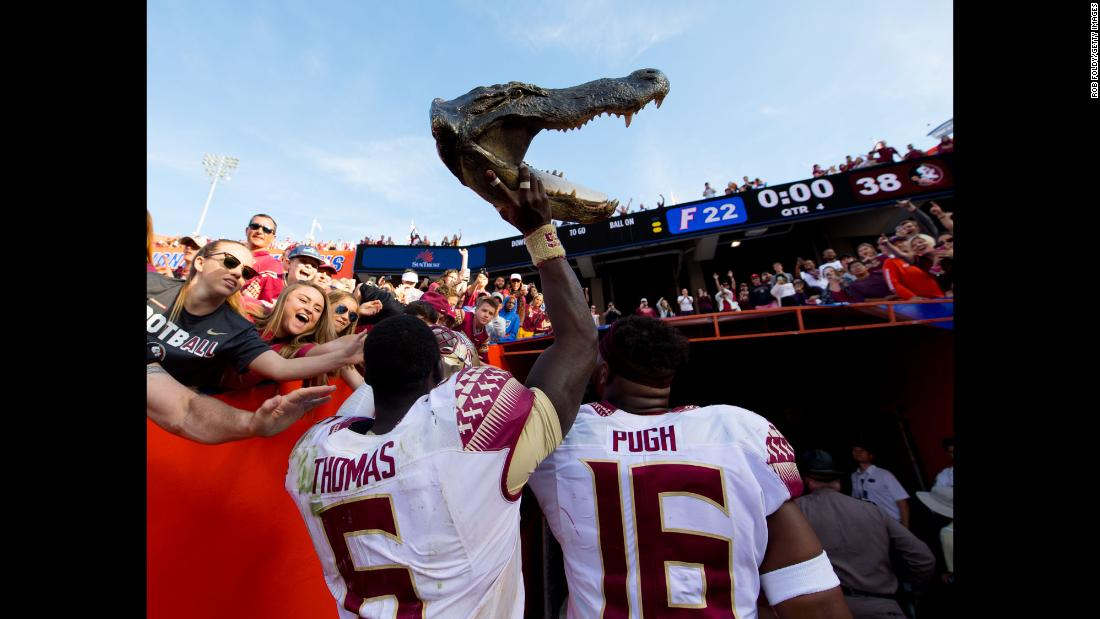 Florida State's Matthew Thomas carries a alligator head out of Ben Hill Griffin Stadium after the Seminoles defeated their rivals, the Florida Gators, on Saturday, November 25.
