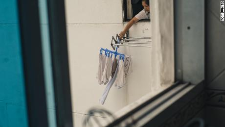A foreign domestic worker hangs washing from the window of a condo in Singapore.