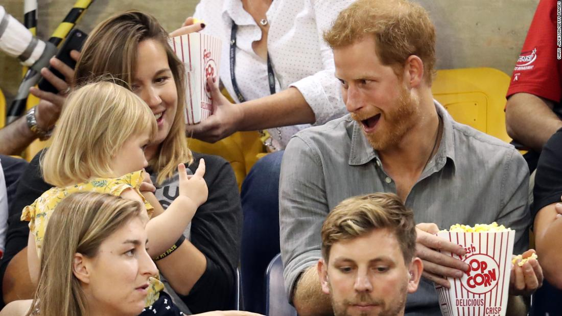 Harry sits with Hayley Henson, left, and her daughter Emily during the Invictus Games in Toronto in September. Hayley is married to British paralympian David Henson, and young Emily was sneaking bites of the prince's popcorn. Harry founded the Invictus Games, an international sporting competition for injured service members.