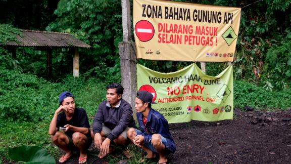 Residents at Gesing village are seen sitting in front of a sign restricting entry to the area on November 27, in Karangasem, Bali, Indonesia.