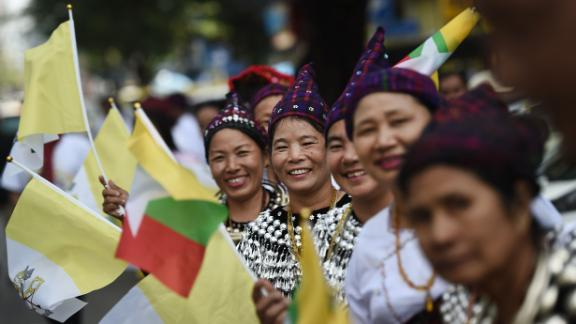 Women in traditional dress line the streets as the Pope leaves Yangon International Airport.