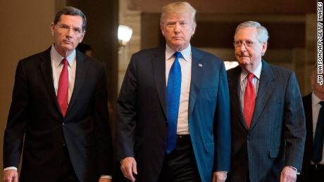 US President Donald Trump (C) with Senate Majority Leader Mitch McConnell (R) and US Senator John Barrasso (L), Republican of Wyoming, arrive for a meeting with the Republican Senate Caucus at the US Capitol in Washington, DC, November 28, 2017. / AFP PHOTO / JIM WATSON        (Photo credit should read JIM WATSON/AFP/Getty Images)