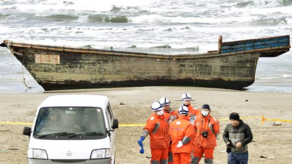 Japanese officials gather on Nov. 27, 2017, near a boat washed ashore in Oga, Akita Prefecture. Authorities found eight bodies in the unidentified wooden boat.