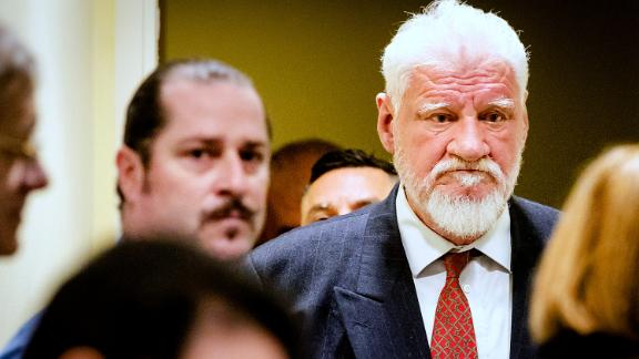 Slobodan Praljak enters the Yugoslav War Crimes Tribunal in The Hague, Netherlands, Wednesday, Nov. 29, 2017, to hear the verdict in the appeals case. The hearing was suspended after Praljak claimed to have drunk poison and shouted that he was not a war criminal, after his 20-year sentence was upheld. A United Nations war crimes tribunal handed down its last judgment, in an appeal by six Bosnian Croat political and military leaders who were convicted in 2013 of persecuting, expelling and murdering Muslims during Bosnia's war in the tribunal's last case. (Robin van Lonkhuijsen/Pool/AP)