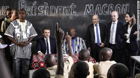 School children rise their hands as French President Emmanuel Macron (left) and Burkina Faso's President Roch Marc Christian Kabore (center) visit a school Tuesday in Ouagadougou.