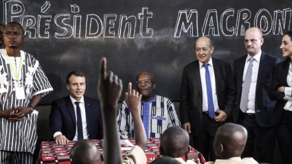 School children rise their hands as French President Emmanuel Macron (left) and Burkina Faso