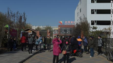 People stand in front of the main gate of the RYB Education New World kindergarten in Beijing on November 24, 2017.