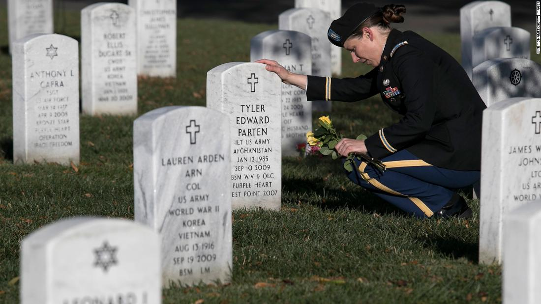 On Veterans Day, Army Capt. Heather Kaiser visits the gravesite of Army Lt. Tyler Parten at Arlington National Cemetery in Arlington, Virginia.