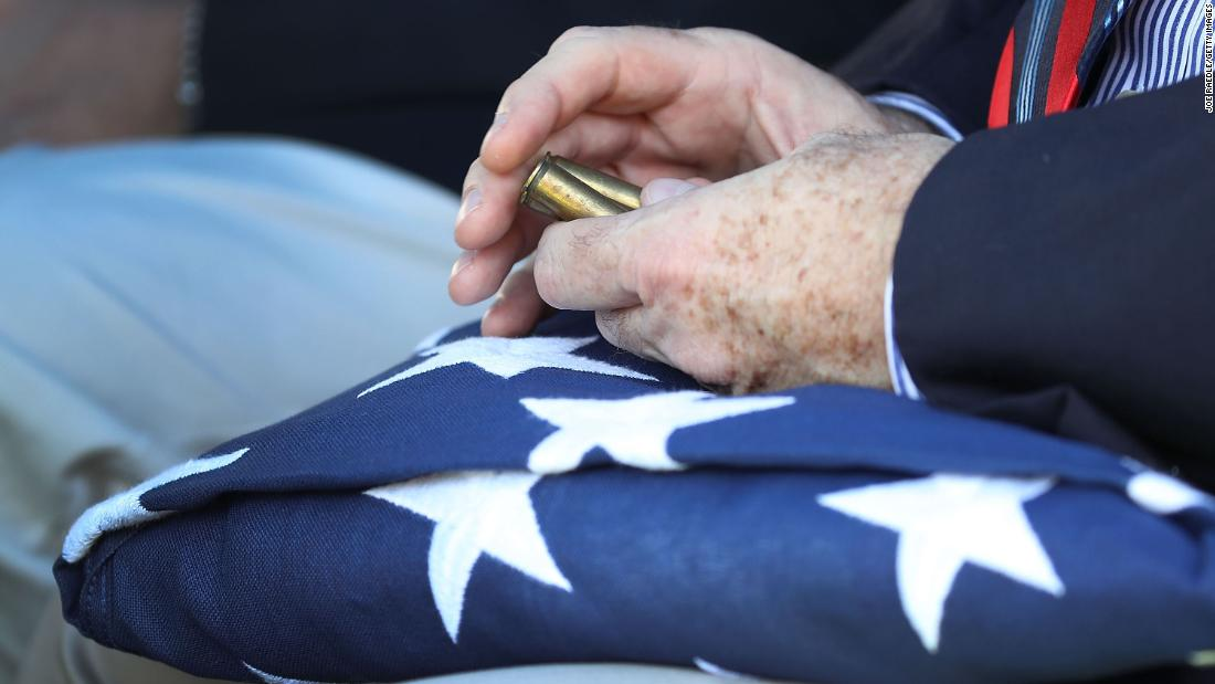 "Lewis Sowell Jr., the nephew of Army Sgt. Richard ""Tiny"" Sowell, holds a folded American flag and the shell casing from a 21-gun salute as his uncle's remains are buried in West Palm Beach, Florida, on Friday, November 10. Sowell was killed in July 1944 when a Japanese mortar hit him during the battle for the Japanese island of Saipan. He had been buried as an unknown soldier in Hawaii until last year, when a DNA match from a family member identified him."