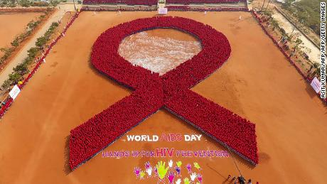 In this aerial photograph made using a drone, students from Indian tribal school, Kalinga Institute of Social Science (KISS) participate in forming a red ribbon, the symbol of HIV/AIDS, in an attempt to make a Guinness Book record on the occasion of World AIDS Day, in Bhubaneswar on December 1, 2016.  World AIDS Day is celebrated on December 1, every year to raise awareness about HIV/AIDS and to demonstrate international solidarity in the face of the pandemic. / AFP PHOTO / ASIT KUMAR        (Photo credit should read ASIT KUMAR/AFP/Getty Images)